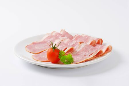 uncooked bacon: plate of fresh bacon slices Stock Photo