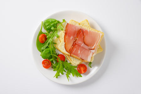 salad greens: slices of white bread with schwarzwald ham, salad greens and halved cherry tomatoes on white plate