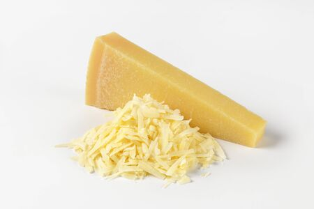 grated parmesan cheese: grated parmesan cheese and wedge on white background