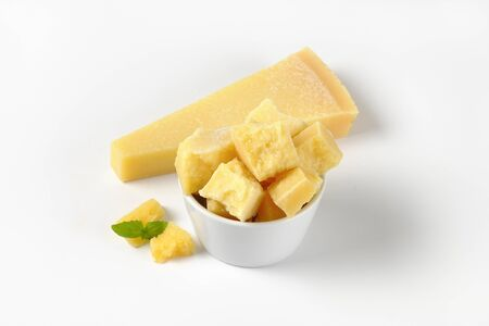 wedge: bowl and wedge of fresh parmesan cheese on white background