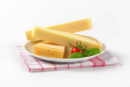 dishtowel: three wedges of parmesan cheese on white plate Stock Photo