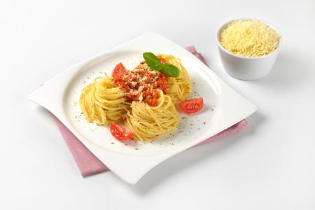 bord gekookte spaghetti met tomatenpesto en kom geraspte parmezaanse kaas Stockfoto