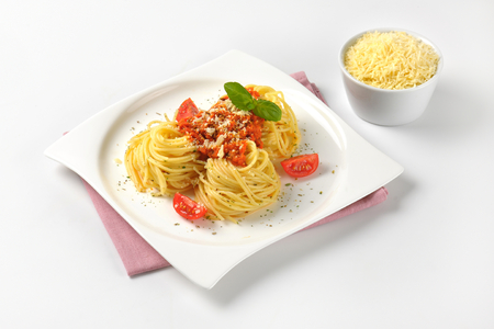 sauce dish: plate of cooked spaghetti with tomato pesto and bowl of grated parmesan cheese