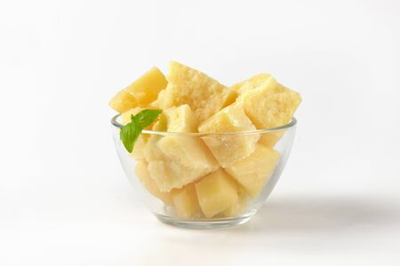 bowl of parmesan cheese pieces on white background