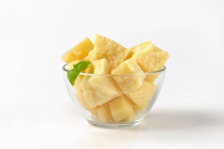 ciotola di pezzi di formaggio parmigiano su sfondo bianco