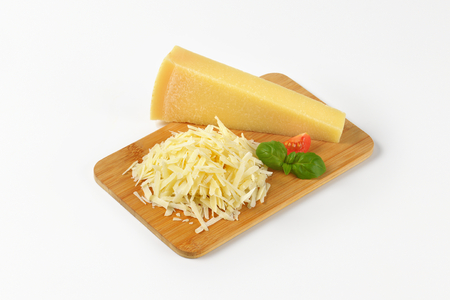 shredding: grated parmesan cheese on wooden cutting board Stock Photo