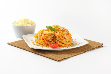 grated parmesan cheese: plate of cooked spaghetti with red pesto and grated parmesan cheese on brown place mat