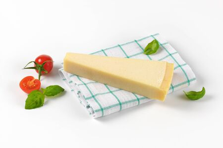 dishtowel: wedge of fresh parmesan cheese and cherry tomatoes on checkered dishtowel