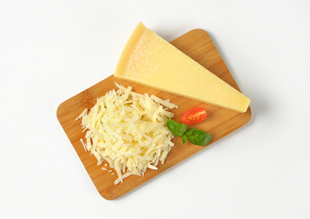 grated parmesan cheese: grated parmesan cheese on wooden cutting board Stock Photo