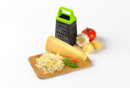 grated parmesan cheese: grater and heap of grated parmesan cheese on wooden cutting board Stock Photo