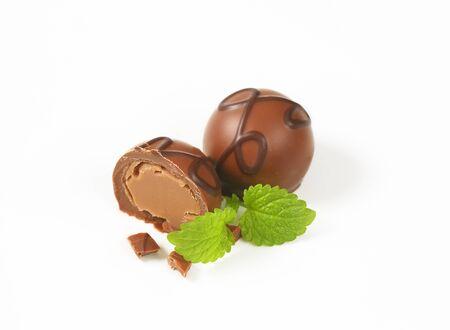 pralines: one and half belgian chocolate pralines on white background