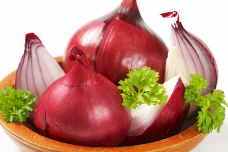 cebollas: enteros y cebollas rojas en cuartos Foto de archivo