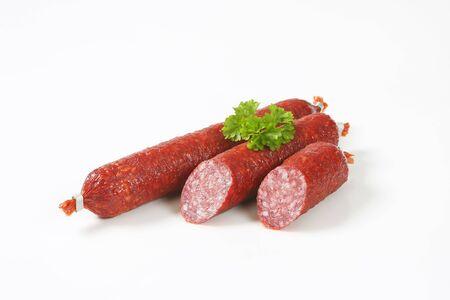 halved  half: fresh salami sausages on white background