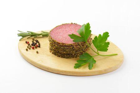 pepper salami: sliced pepper coated salami and peppercorns on wooden cutting board