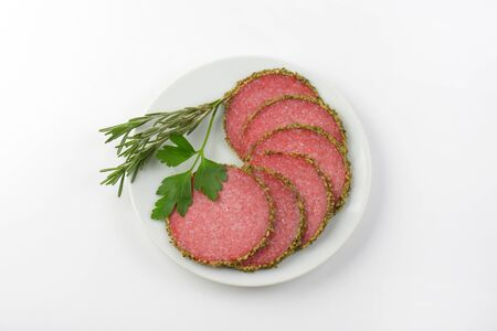coated: slices of green pepper coated salami on white plate