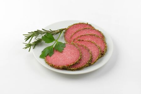 pepper salami: slices of green pepper coated salami on white plate