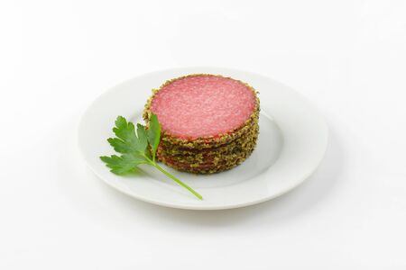 pepper salami: stack of sliced pepper salami on white plate