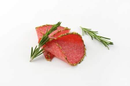 pepper salami: slices of green pepper coated salami with rosemary on white background