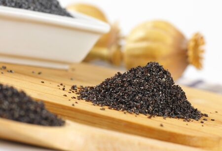 poppy seeds: heap of ground poppy seeds on wooden cutting board