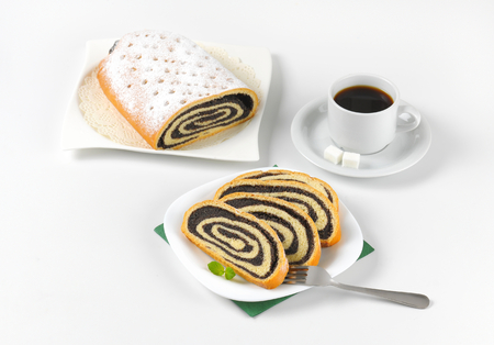 poppy seed: sliced poppy seed roll and cup of coffee Stock Photo