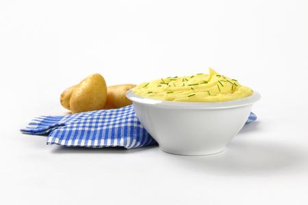 dishtowel: bowl of potato puree with chopped chives and raw potatoes Stock Photo