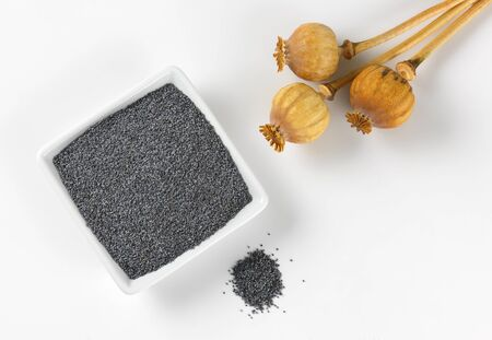 poppy seeds: bowl of whole poppy seeds and three dried seed heads Stock Photo