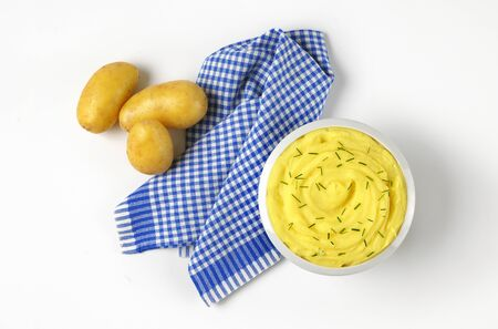Plato de puré de patatas con cebollino picado y patatas crudas Foto de archivo - 57997222