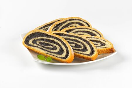 poppy seed: slices of poppy seed roll on white plate