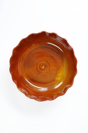 scalloped: scalloped edge brown pottery bowl on white background