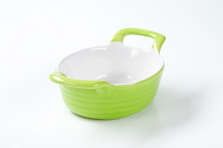 casserole dish: oval casserole dish with two handles, green on the outside