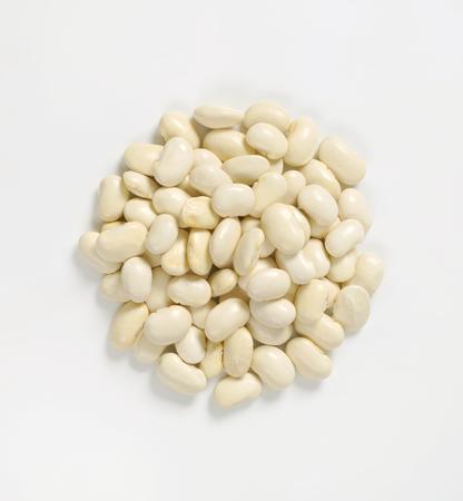 mucchio di fagioli bianchi crude su sfondo bianco