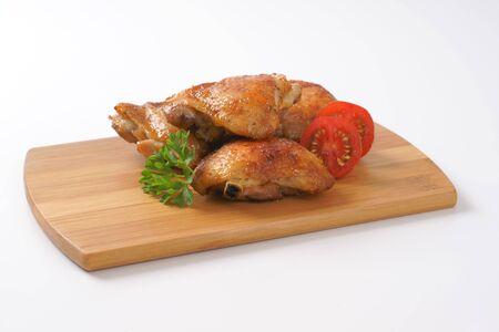 muslos: muslos de pollo asado en tabla para cortar