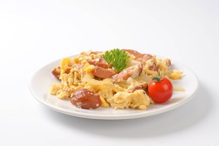 huevos revueltos: plate of scrambled eggs with onion and sliced sausage