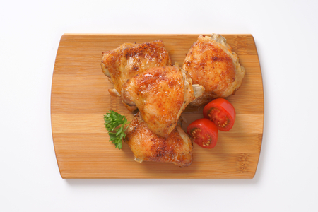 thighs: muslos de pollo asado en tabla para cortar