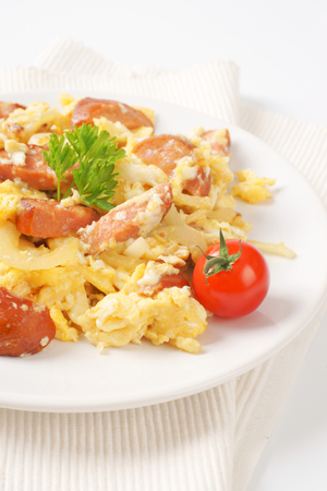 scrambled eggs: plate of scrambled eggs with onion and sliced sausage