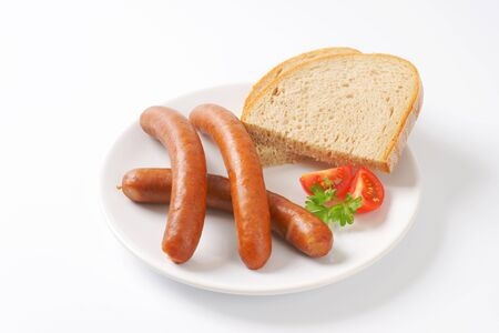 long shots: cooked sausages with slices of continental bread Stock Photo