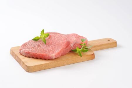loin chops: raw boneless pork loin chops on cutting board Stock Photo