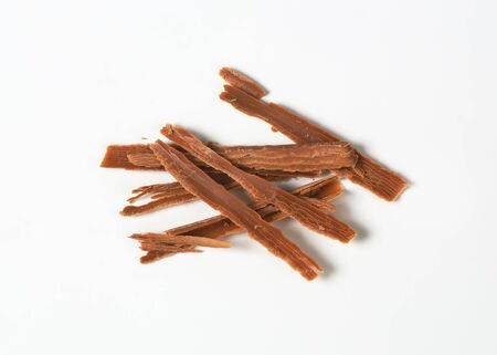 shavings: handful of chocolate shavings on white background Stock Photo