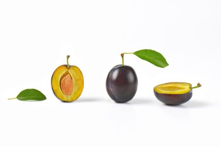 halved: whole and halved plums on white background Stock Photo