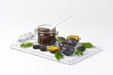 dried plums: plum jam, fresh and dried plums on wooden cutting board