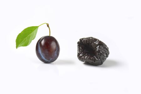 prune: one fresh plum and one prune on white background Stock Photo