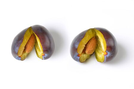 halved: two halved ripe plums on white background