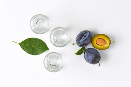 shot glasses: Plum brandy (slivovitz) in shot glasses and fresh damson plums