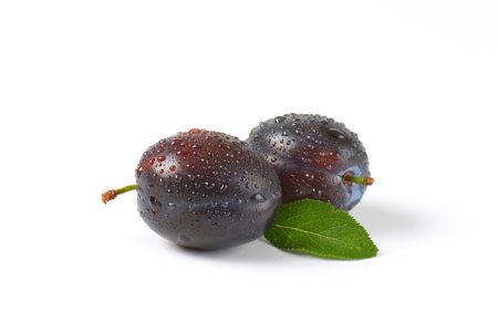white washed: two washed plums on white background
