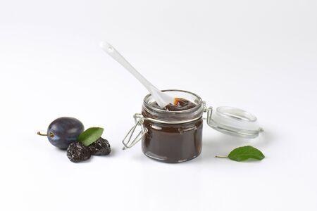 ciruela pasa: cuchara blanca en un tarro de mermelada de ciruela