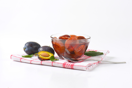 dishcloth: Damson compote in a glass bowl and fresh plums next to it on checked dishcloth
