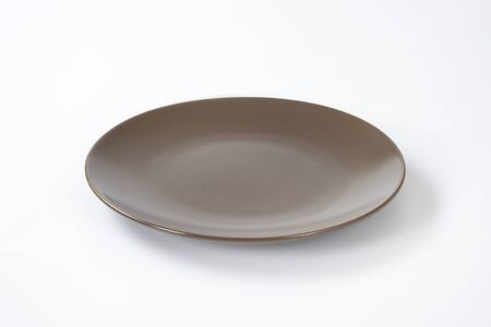 rimless: Empty shallow brown breakfast plate Stock Photo
