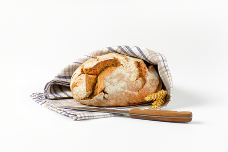 round loaf of bread in checked tea towel and kitchen knife