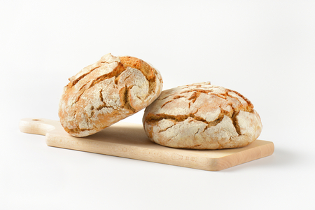 crust crusty: two fresh whole bread cobs on wooden cutting board Stock Photo
