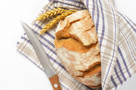 loaf of bread in checked tea towel and kitchen knife